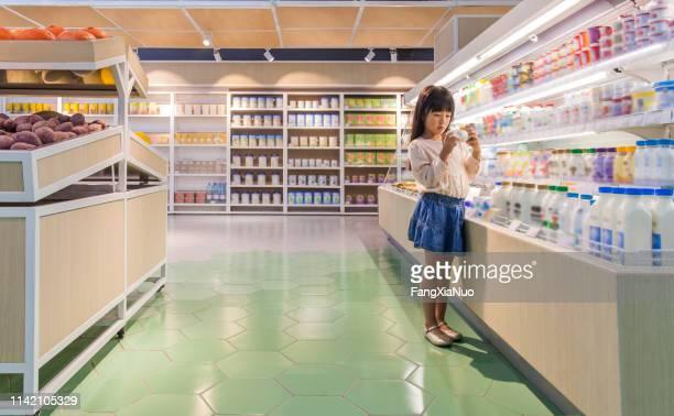 jong meisje het lezen van ingrediënten in de supermarkt - selective focus stockfoto's en -beelden