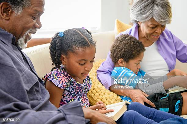 Young girl reading to African American grandfather on sofa