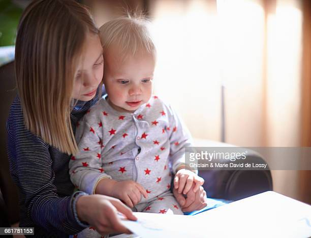 Young girl reading to baby brother