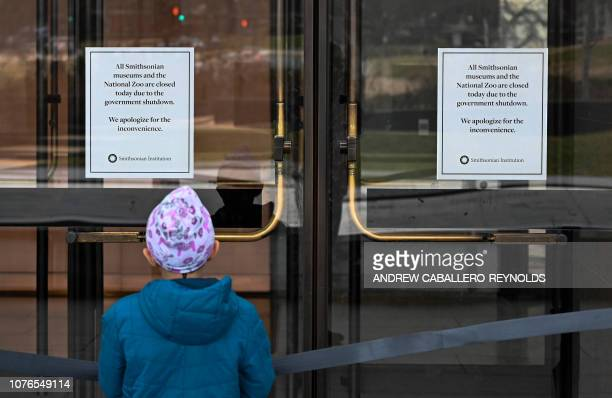 A young girl reads a sign posted on the door of The National Museum of African American History stating that all Smithsonian Museums are closed due...