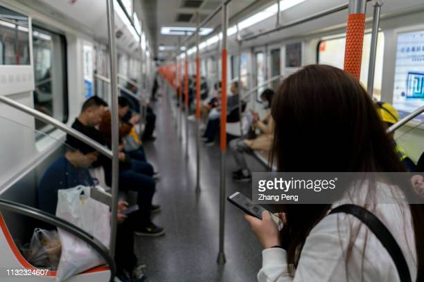 Young girl reads on mobile phone in subway train Young people are addicted to mobile phones arousing a lot of social problems such as escaping from...