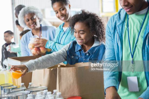 young girl receives donations while volunteering in food bank - homeless shelter stock pictures, royalty-free photos & images
