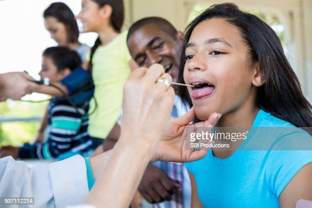 young girl receives medical exam at free clinic - film and television screening stock pictures, royalty-free photos & images