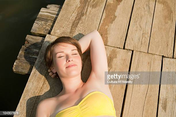 Young girl relaxing and sunning on pier