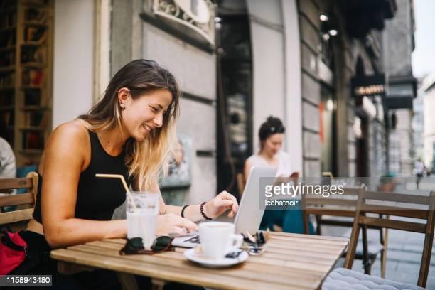カフェでくつろいだ若い女の子、オンラインショッピングをする - セルビア ベオグラード ストックフォトと画像