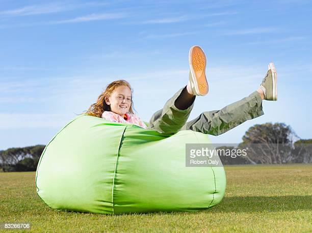 Young girl relaxing in bean bag outdoors