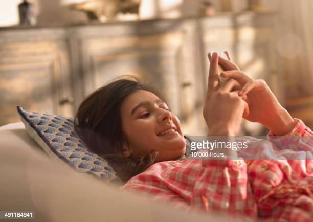 A young girl relaxing looking at her phone