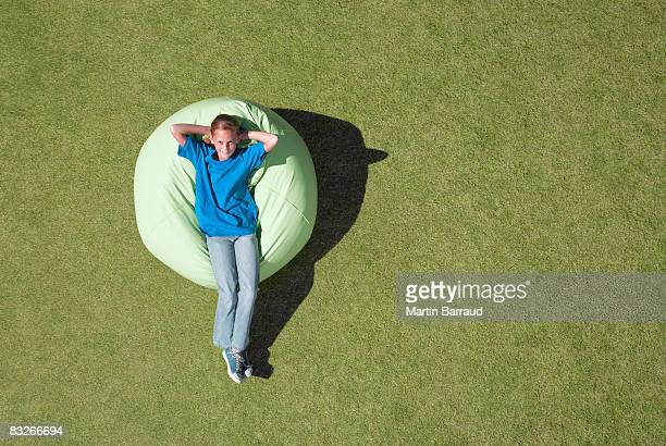 Young girl relaxing outdoors in bean bag