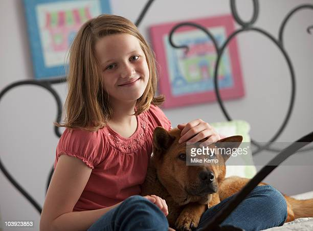 Young girl relaxing with dog on bed