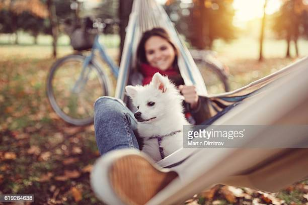 Young girl resting in hammock with little dog
