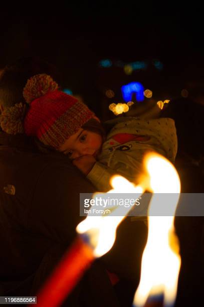 A young girl rests during New Year's Eve celebrations at the Flamborough Fire Festival on December 31 2019 in Flamborough England Now in its fifth...