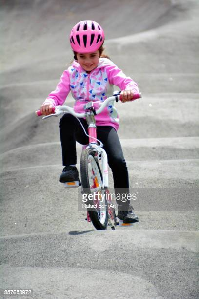 Young girl rides a bicycle in a bike park