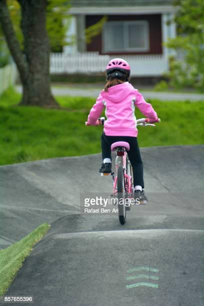 young girl rides a bicycle in a bike park - rafael ben ari fotografías e imágenes de stock