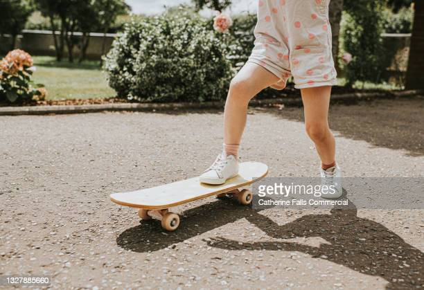 a young girl rides a small skateboard with ease - human joint stock pictures, royalty-free photos & images