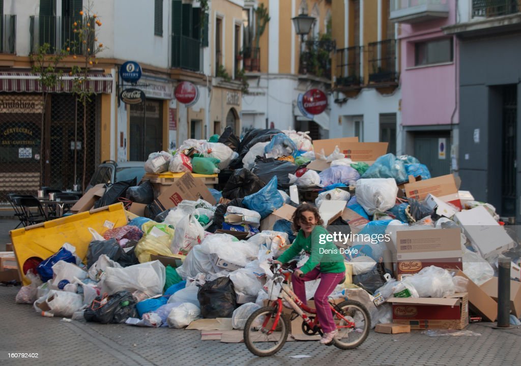 A young girl rides her bike past a mound of garbage during the ninth day of the Seville waste disposal strike on February 5, 2013 in Seville, Spain. Workers are striking over demands they take a 5% pay cut and extend their working week to 37.5 hours.