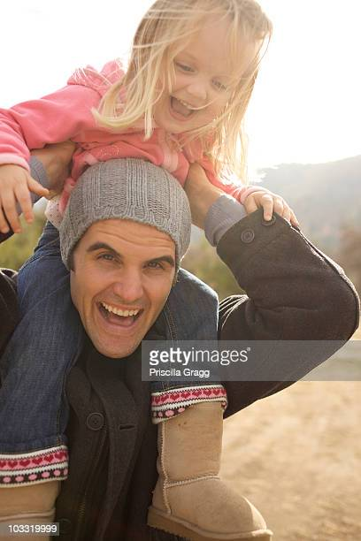 young girl rides her uncle's shoulders. - niece stock photos and pictures