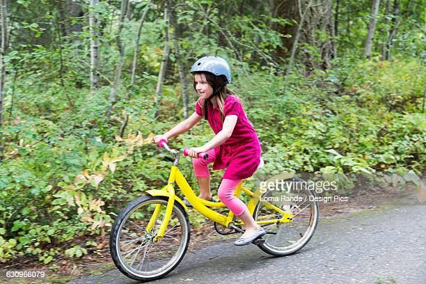 A young girl rides her yellow bicycle on a trail