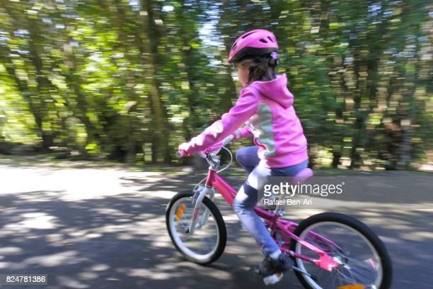 young girl rides on a bike in a park - rafael ben ari fotografías e imágenes de stock