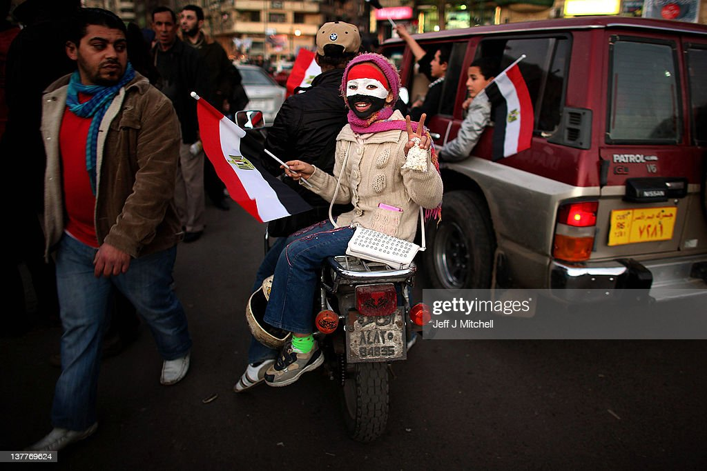 A young girl rides on the back of a motorcycle through Tahrir Square on January 26, 2012 in Cairo, Egypt. Tens of thousands of Egyptian people gathered yesterday to celebrate the anniversary of the start of the uprising which ended President Hosni Mubarak's rule.