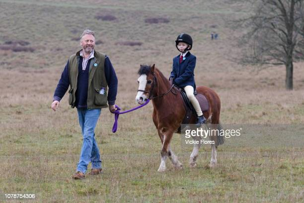 A young girl riding a pony is led by a man as she arrives for the traditional Chiddingfold Leconfield and Cowdray Boxing Day Hunt which sets off from...