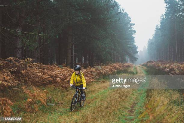 young girl riding bike in forest - headwear stock pictures, royalty-free photos & images