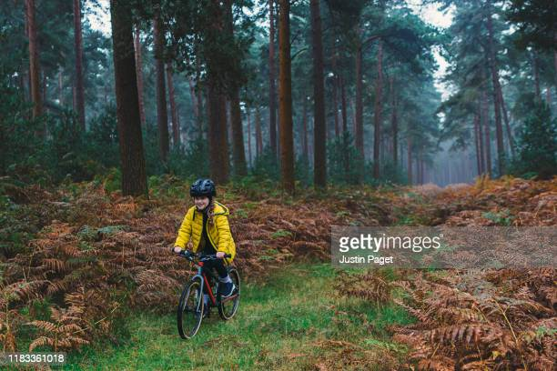 young girl riding bike in forest - reality fernsehen stock pictures, royalty-free photos & images