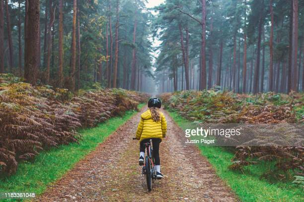 young girl riding bike in forest - human head stock pictures, royalty-free photos & images
