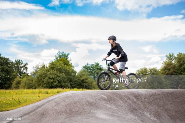 young girl riding bmx bicycle - bmx cycling stock pictures, royalty-free photos & images