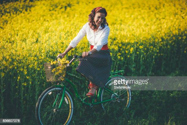 young girl riding her green retro hipster bike - brassica stock photos and pictures