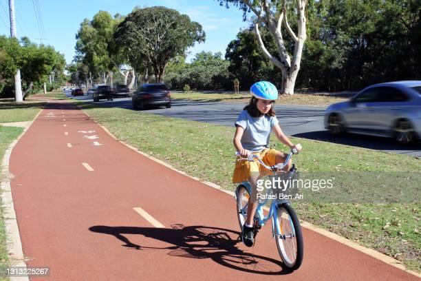 young girl riding on a city bicycle path front view - rafael ben ari stock-fotos und bilder
