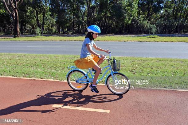 young girl riding on a city bicycle path side view - rafael ben ari stockfoto's en -beelden