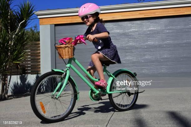young girl riding on bike - rafael ben ari stock-fotos und bilder