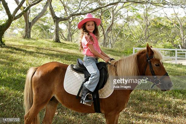 young girl riding pony - cowgirl hairstyles stock photos and pictures