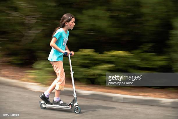 Young girl riding scooter in suburban street