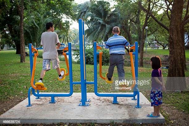 A young girl right watches men center exercise at Lumphini Park in Bangkok Thailand on Sunday March 15 2015 Almost a third of Thailand's population...