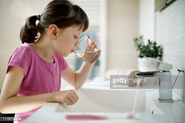 young girl rinsing mouth in the bathroom - mouthwash stock pictures, royalty-free photos & images