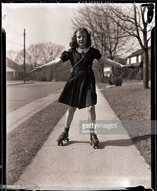 A young girl roller skates on the sidewalk She is wearing a kneelength plaid dress Undated photograph circa 1950's