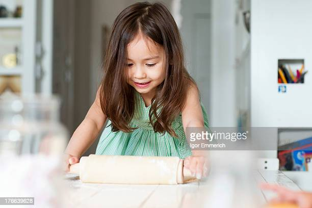 Young girl rolling out pastry on kitchen counter