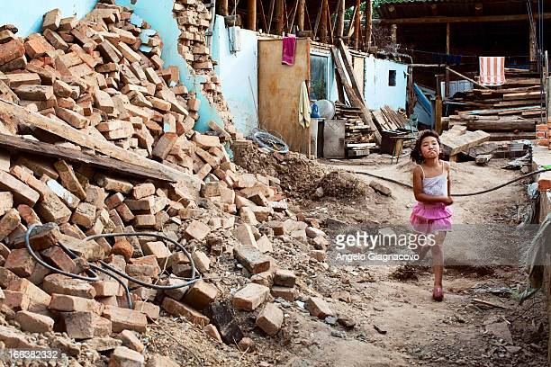 CONTENT] Young girl running across the ruins of a collapsed house in Karakol Kyrgyzstan