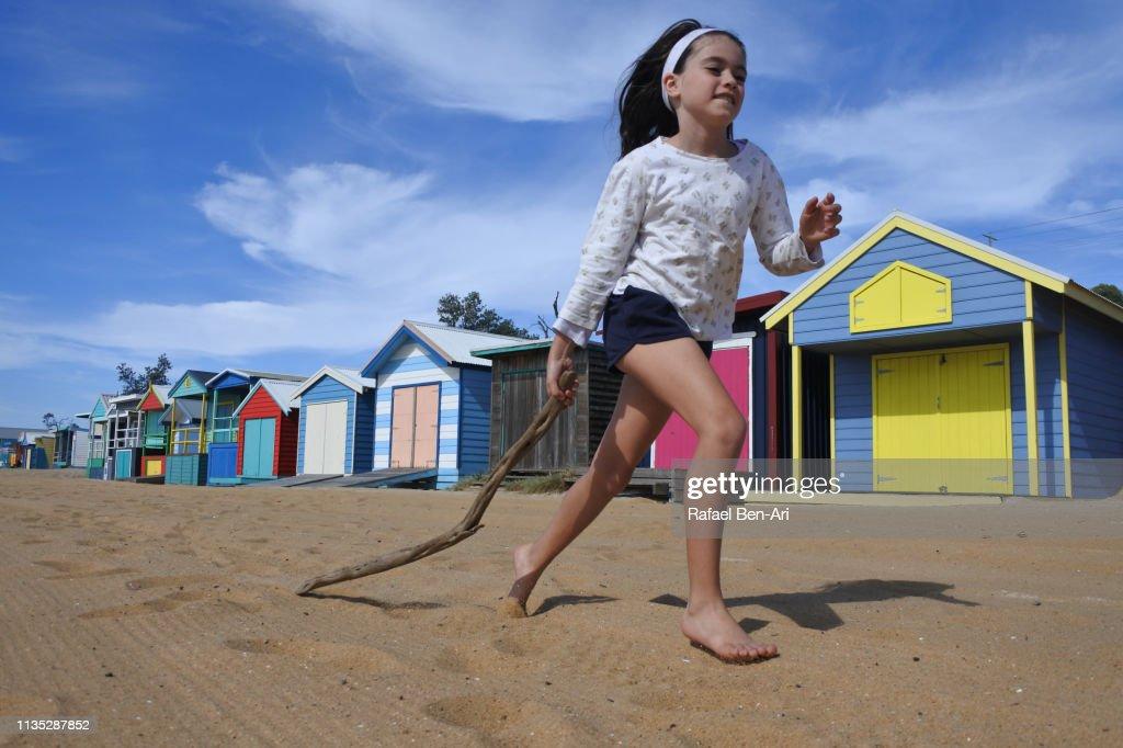 Young girl running along the Iconic Bathing Boxes of the Mornington Peninsula Victoria Australia : Stock Photo