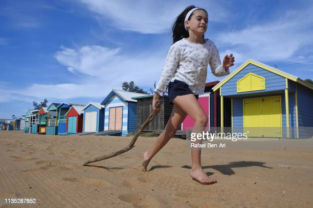 Young girl running along the Iconic Bathing Boxes of the Mornington Peninsula Victoria Australia