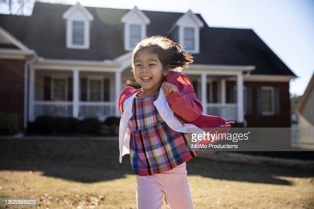 young girl running and laughing in front yard - mortgage stock pictures, royalty-free photos & images