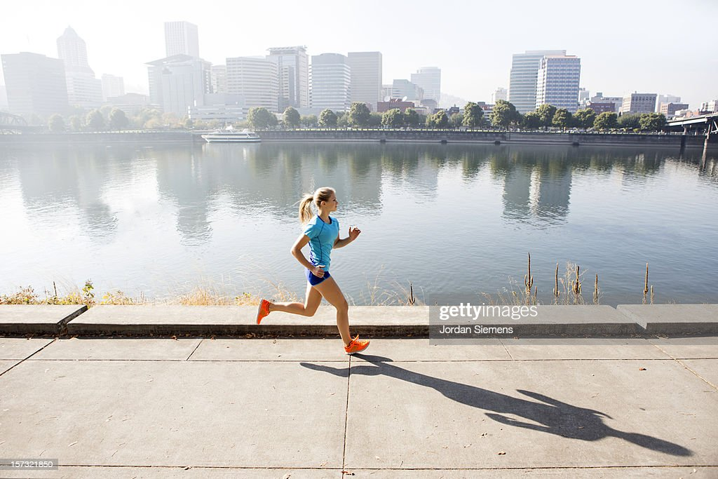 A young girl running for exercise. : Bildbanksbilder