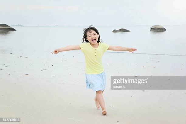 Young girl running freely on sandy beach.