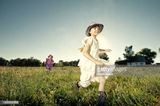 young girl running in a grass field - robb reece stock pictures, royalty-free photos & images
