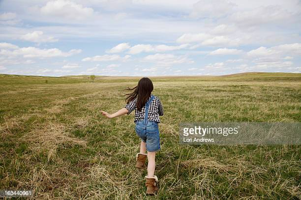 young girl running in green prairie field - lori andrews stock pictures, royalty-free photos & images