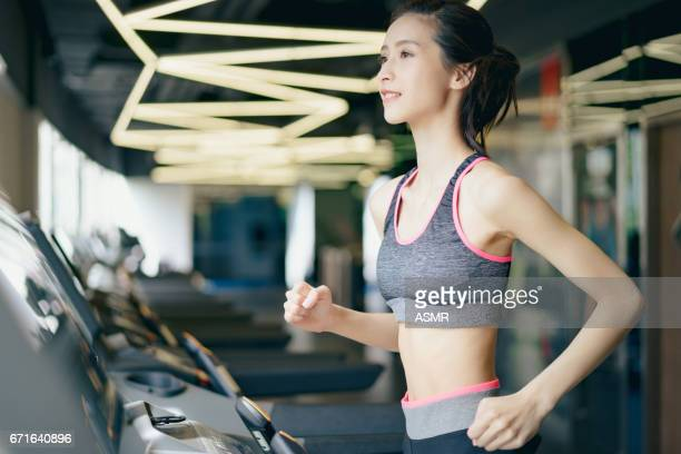 Young girl running on a treadmill in health club