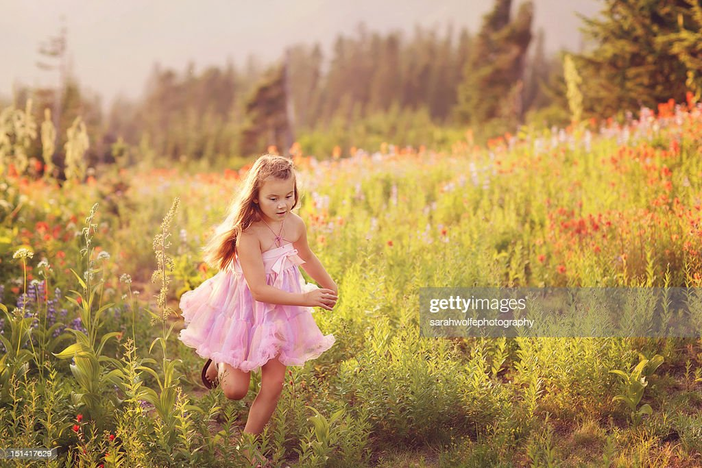 Young girl running through a field : Stockfoto