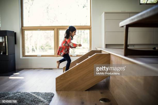 Young girl running up steps at home