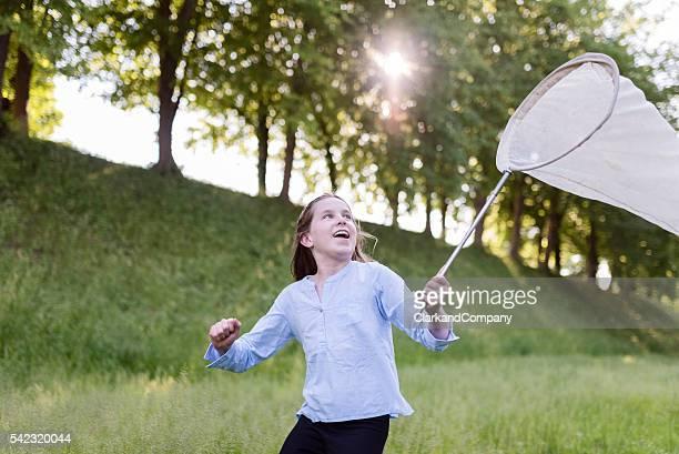 Chica joven corriendo con una mariposa Net.